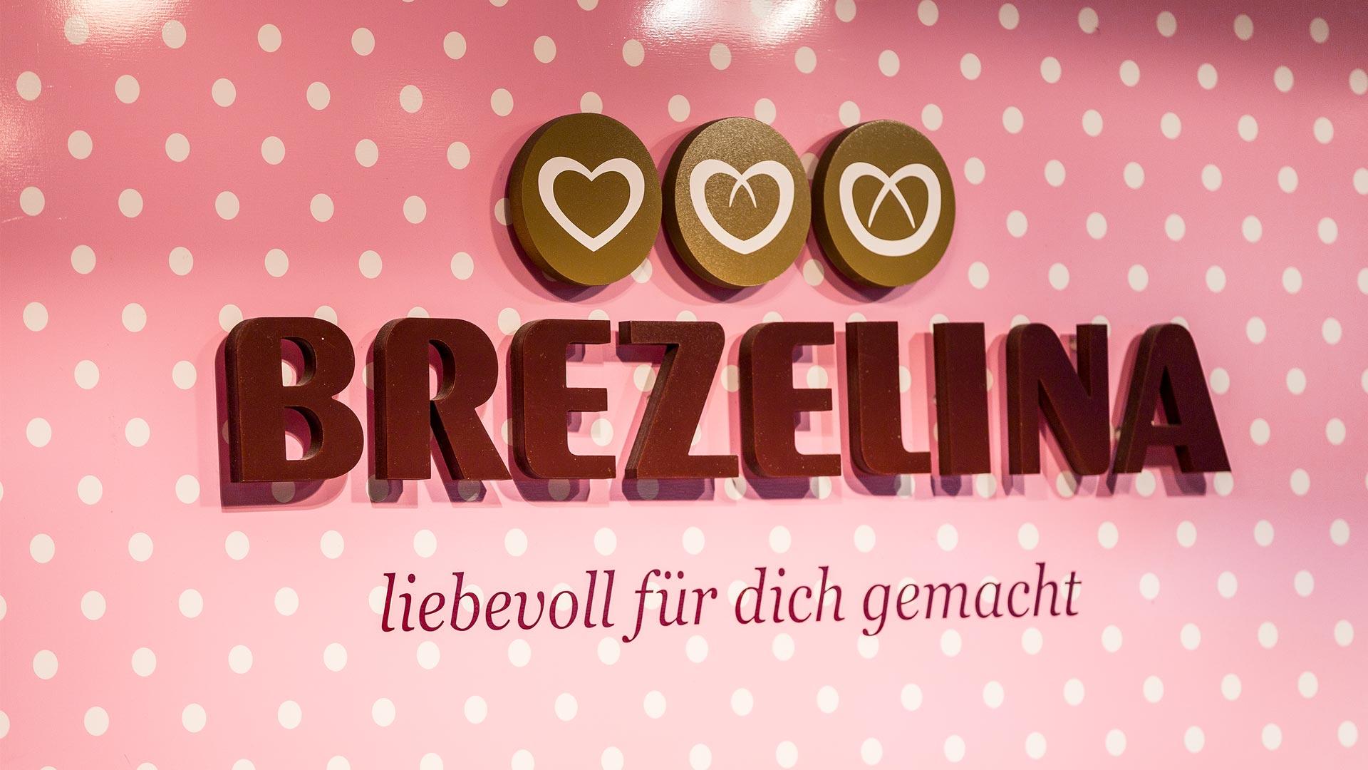 Brezelina Logo und Claim auf rosa-weiß-gepunkteter Wand